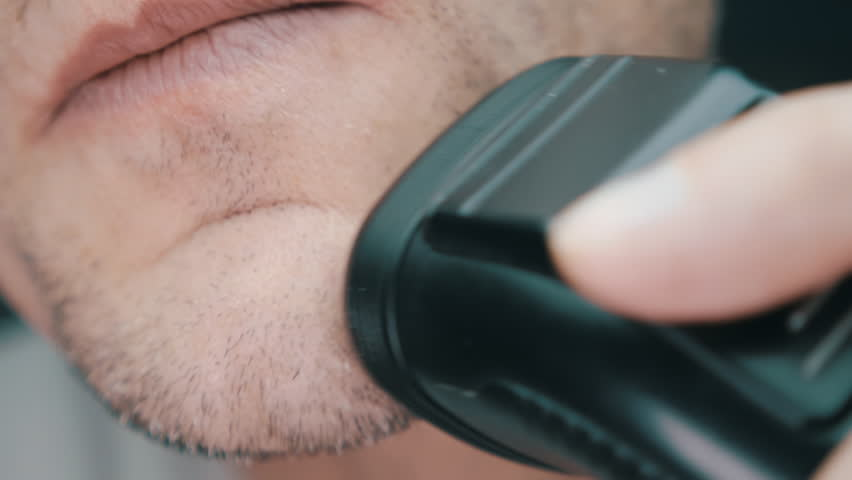 Man shaving beard with electric shaver. Check shaving swiping your finger on the cheek. Closeup. Shallow depth of field