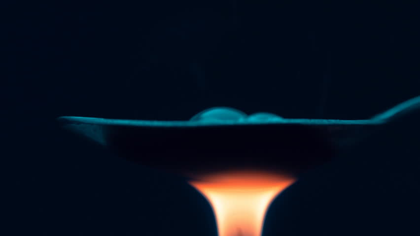 The spoon boiling drug heroin is heated by the flame of a lighter on black background. Closeup. Shallow depth of field
