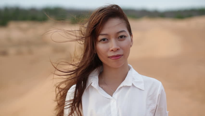 Asian woman smile outdoor desert wind blowing hair, wear white shirt close up face of young happy girl looking to camera cheerful
