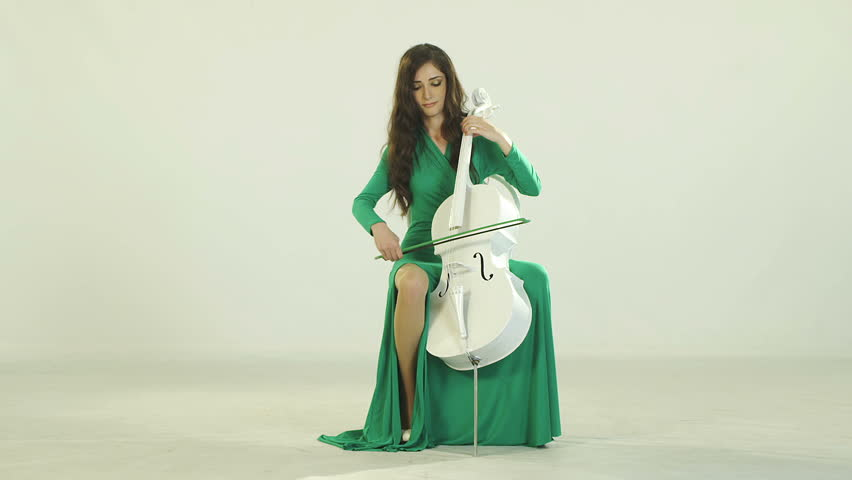 Young musician girl play with cello violoncello in white room. Few shots