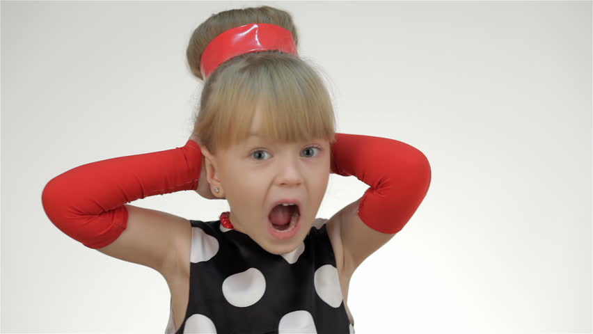 Kid girl covers his ears with his hands and shouted. Kid girl posing in studio isolated on white background. The girl dressed in the summer red polka dot sleeves and arm warmers, hair ribbon. She is