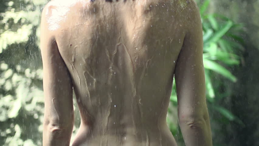 Young naked woman standing under shower, super slow motion, shot at 240fps