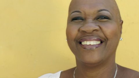 Portrait of black 50 year old woman with shaved head smiling at camera on yellow background