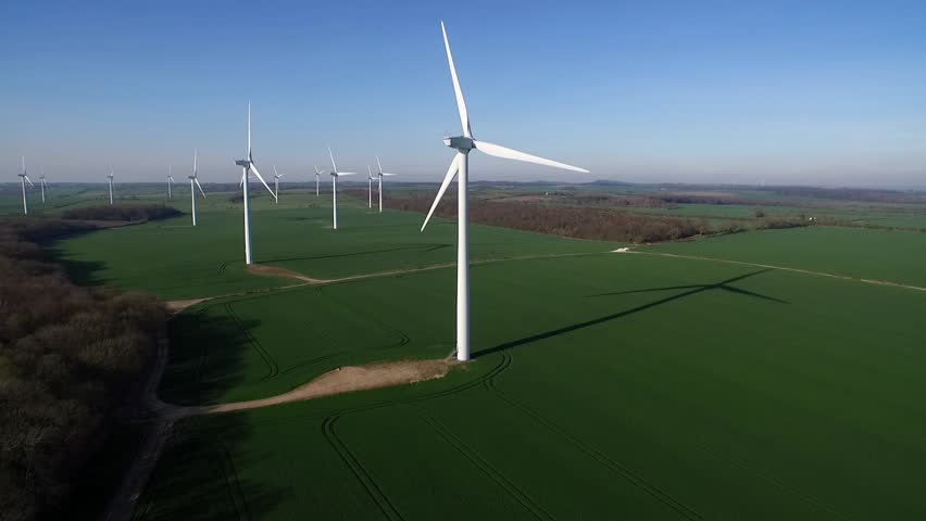Slow pan into back-lit aerial clip of wind turbine farm in rural landscape shot in late evening..