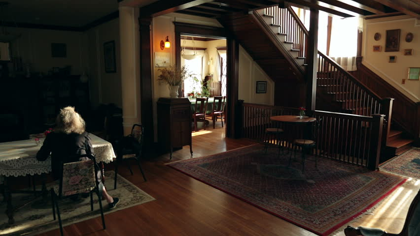 Lobby of attractive old house used for lodging. Sunshine pours into the room. An elder lady sits behind a table, reading.
