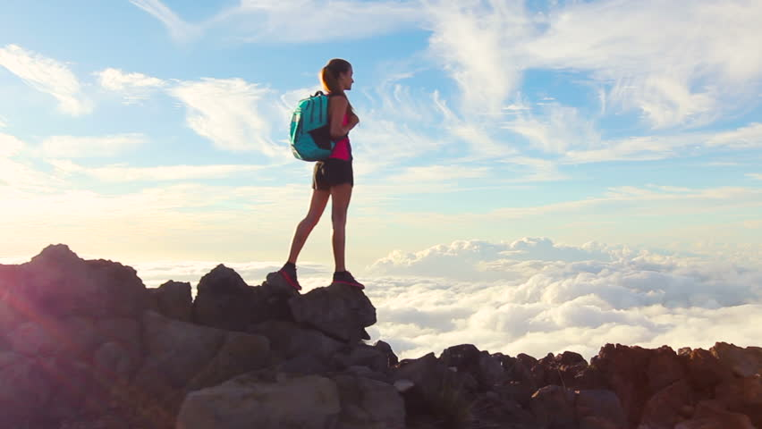 Hiker with Backpack Hiking on top of a mountain with sun flares. Young Woman Healthy Active Lifestyle. Adventure in Nature. | Shutterstock HD Video #12816746