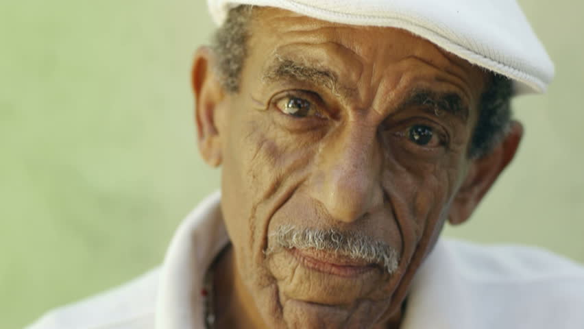 portrait of senior hispanic man with white hat looking at camera against green wall and laughing