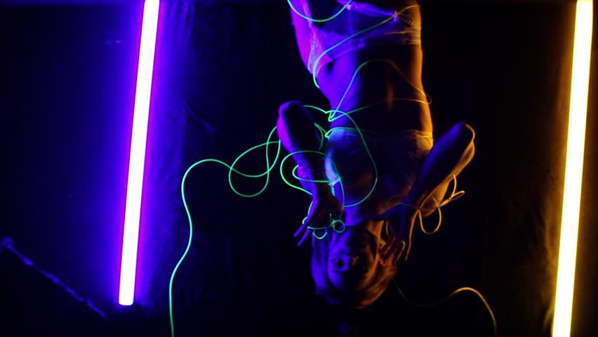 Ariko twirling with glowing wire wearing glow in the dark lingerie upside down.