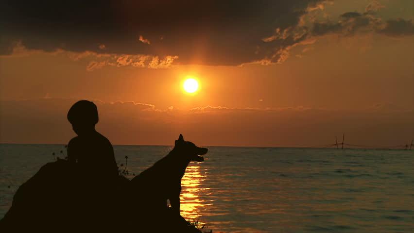Boy and dog sitting near Sea at Sunset