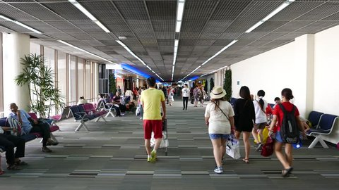 BANGKOK - MARCH 30, 2015: Unidentified asian passengers walk through airport passage, POV walk shot, move forward and pass passageway lounge area, gates access at Don Mueang international airport.
