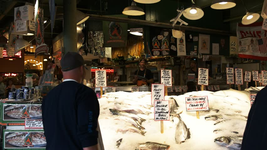 SEATTLE, WASHINGTON, USA – SEPTEMBER 4, 2015: fishmongers throw and catch fresh salmon at pike place market in seattle washington