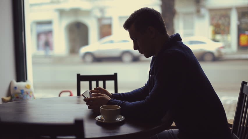 Silhouette of man with Smartphone in cafe  | Shutterstock HD Video #12866927