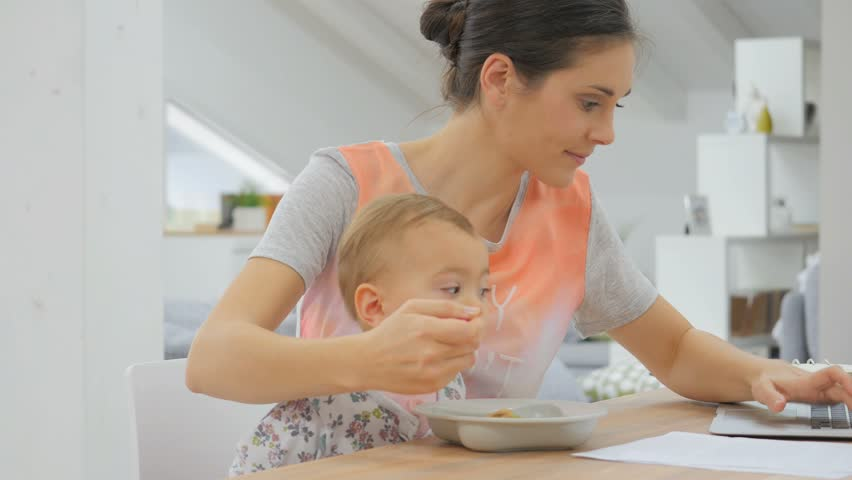 Busy mother trying to work and feed kid at the same time | Shutterstock HD Video #12867863