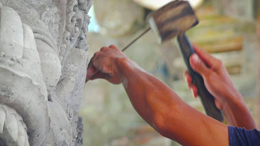Asian sculptor. painstakingly chipping away at fine. intricate details of a stone work of art. using a traditional wooden hammer and simple chisel. Video UltraHD