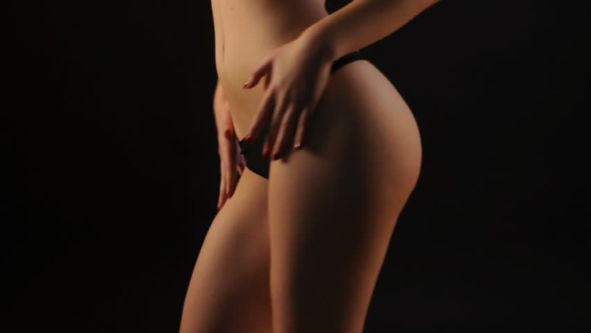 Sexy brunette in black lingerie dancing in the dark.