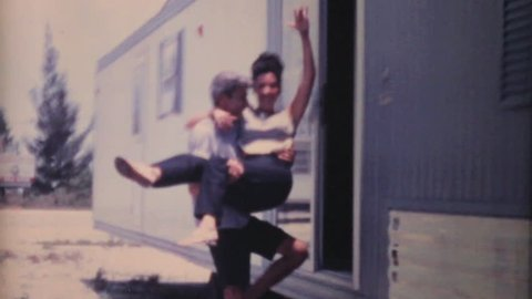 PENSACOLA, FLORIDA, JUNE 1969: A husband and his wife stand proudly in front of their new mobile trailer in Orlando, Florida while on holidays in the summer of 1969.