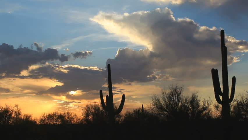 Time Lapse, Clouds swoop across sky as the sun sets over saguaro cactus desert landscape.