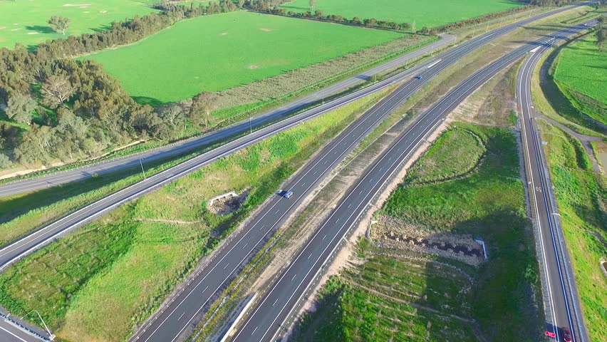Aerial view semi trailer lorry trucks, vehicles & cars with freight transport traveling on outback country high speed freeway or motorway driving on open roadway. Hume Highway Australia