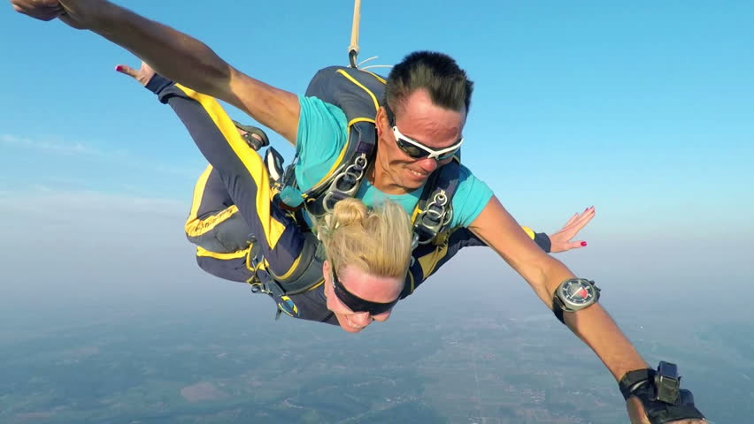 In this video, we can see how a couple is sky diving in the air and how the parachute opens up. The lady is smiling in the video and having a great time.