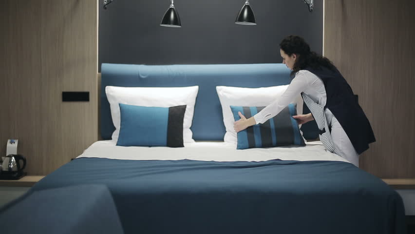 Hotel: Maid making bed in hotel room