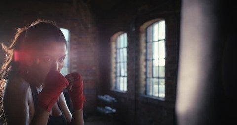 Beautiful Kickboxing woman training punching bag in fitness studio fierce strength fit body slow motion kickboxer series