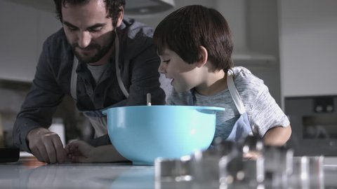 Father and son baking biscuits in Kitchen