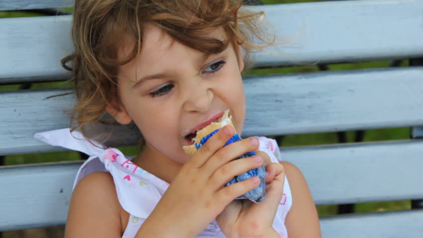 nice little girl eat ice cream and sit on bench at park, says something correcting her hair