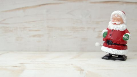 Santa Claus novelty toy HD stock footage. A close up of Father Christmas wind up toy walking across the frame set against a white rustic background.