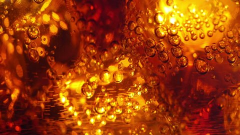 Cola pouring into a glass with ice cubes. close-up. 4K UHD 2160p footage.