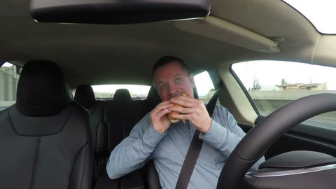 Severely distracted driver, eating lunch and texting while driving. Safety note: this clip was carefully created under controlled conditions.