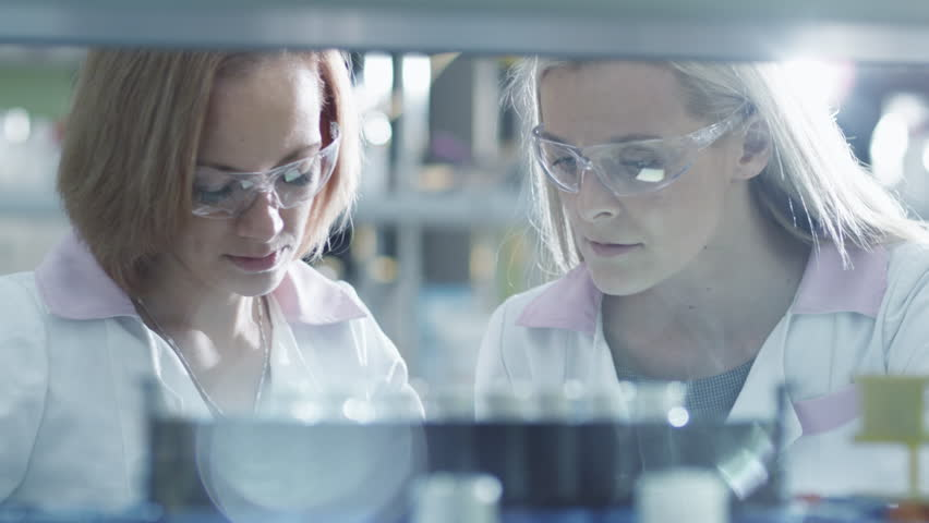 Two female scientists are working with  liquid samples in a tube in a laboratory. Shot on RED Cinema Camera in 4K (UHD).