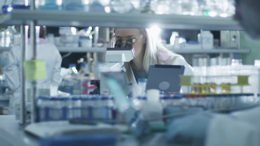 Female scientist is using a microscope and a tablet while working in a laboratory. Shot on RED Cinema Camera in 4K (UHD). | Shutterstock HD Video #13088633