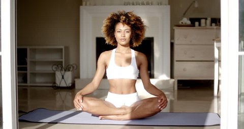 Young woman sitting on lotus position on floor in the room