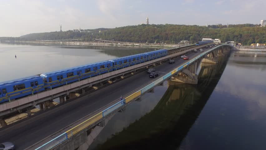 Aerial video. Train in Motion at The Metro Bridge through the Dnipro river in Kiev. Drone footage. 4K.