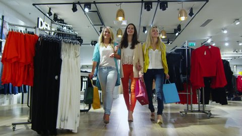 Three cheerful young women are walking through a department store in colorful garments. Shot on RED Cinema Camera in 4K (UHD).