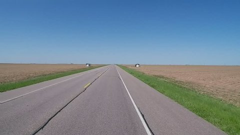 Point of view driving vehicle shot of driving past endless flat farmlands in North Central Texas. A traveler's view of an empty road in the middle of nowhere that stretches forever to horizon.