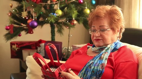 Christmas Gift -   Sulky senior woman lying on a sofa near the christmas tree,  opening gift disappointed and unhappy,