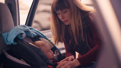 A young mother unbuckling her baby daughter from her car seat