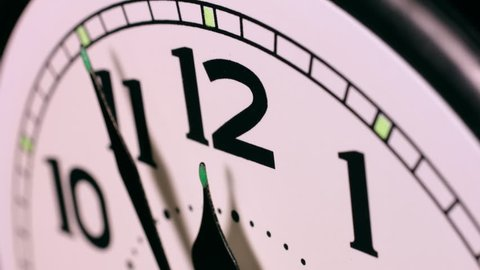 Close up time lapse of clock hands passing 12 o'clock midnight. End of one day and the beginning of the new day.