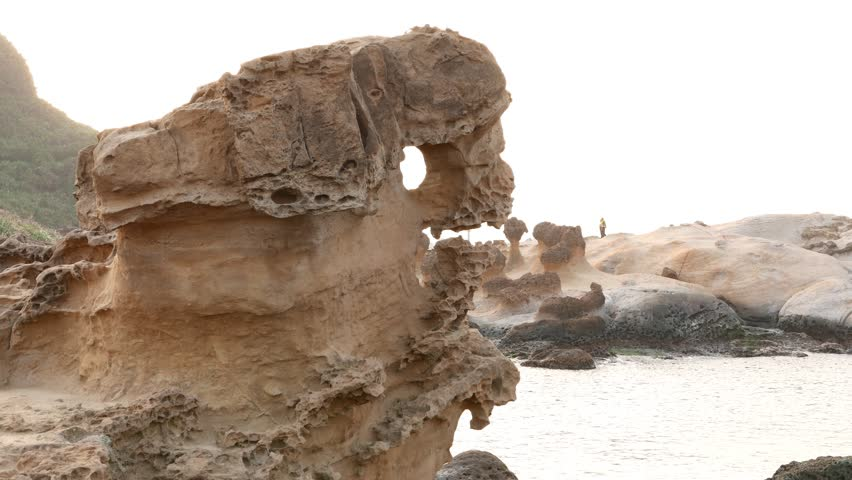 Closeup eroded sandstone formation at Yehliu Geopark cape. Sea waters on background, pan right to rocky shore view. Geological forces and years of erosion create many odd formations in this area #13145591