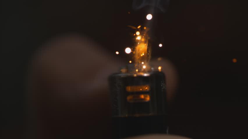 Lighter (black) sparking and lighting from the front - top cut off macro in slow motion shot at 1000 frames per second on a Phantom Flex 4k - alpha matte - black background