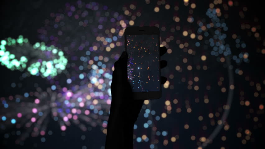 Silhouette of hand recording fireworks with smartphone on black screen | Shutterstock HD Video #13171427