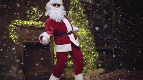 Santa Claus in sunglasses dancing and looking at the camera, tracking shot, snowflakes, christmas tree with lights and decorated fireplace in background