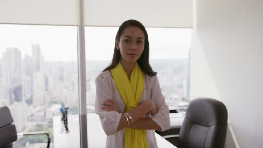Adult businesswoman leaning on desk in modern office with beautiful sight of the city. The secretary smiles to the camera and crosses arms. Medium shot, Slow motion, steadicam shot   Shutterstock HD Video #13183967