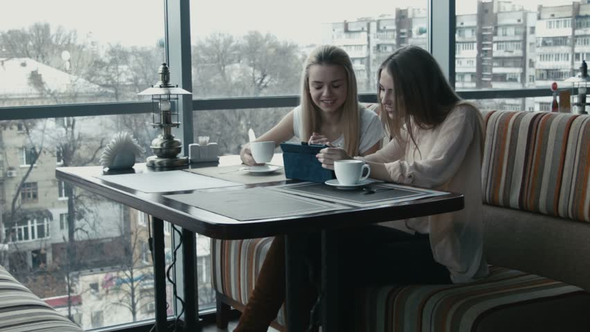 The girl shows to the girlfriend something on the touchpad in cafe #13189217