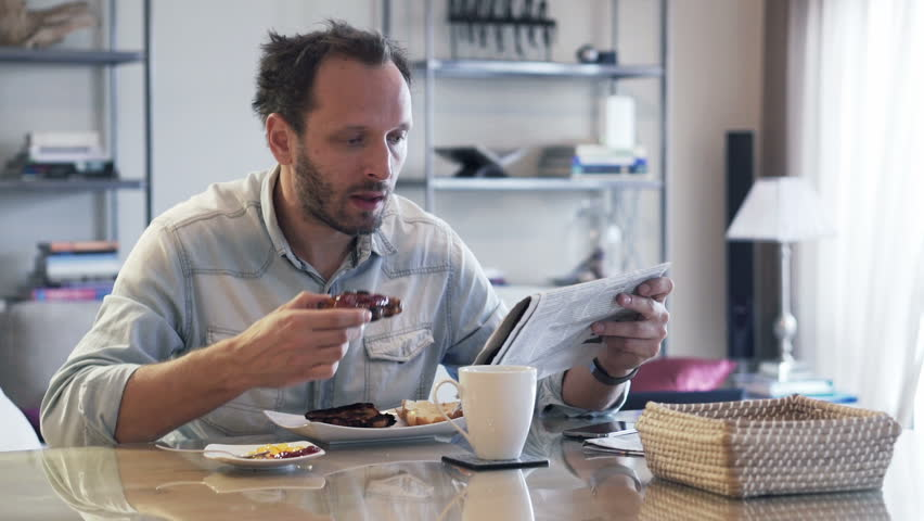 Young man reading newspaper during breakfast at home
