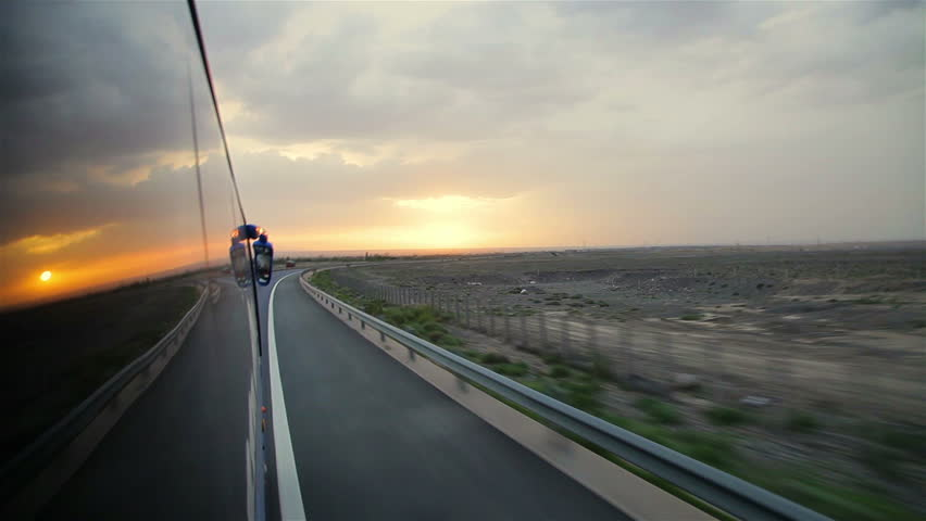 Bus runs on the highway at sunset,China.
