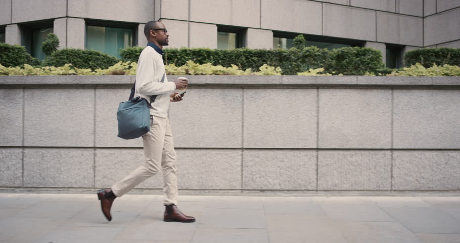 African American Man sms texting using app on smart phone in city. Handsome young businessman drinking coffee using smartphone smiling happy. Urban male professional commuting in his 20s | Shutterstock HD Video #13200074