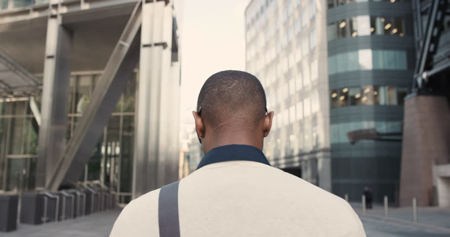 Rear view african american businessman walking in city commuting independently between glass buildings