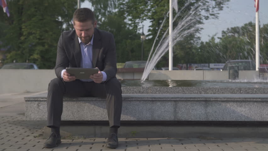Businessman sitting on wall browsing tablet against fountain.